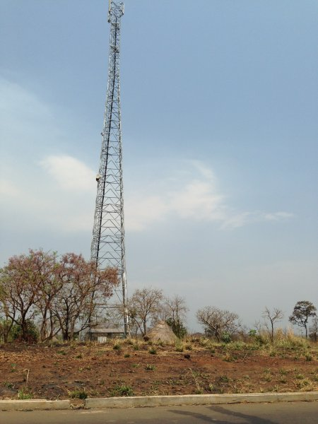 Cell tower dwarfs traditional home.