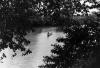 Canoe on Baro w branches (photo Steven Schewe) .